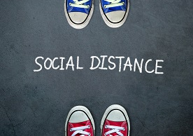 """blue sneakers and red sneakers facing each other with """"Social Distance"""" written in between"""
