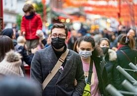 image of a street crowd with some people wearing maskes to protect against COVID-19