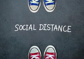 "blue sneakers and red sneakers facing each other with ""Social Distance"" written in between"